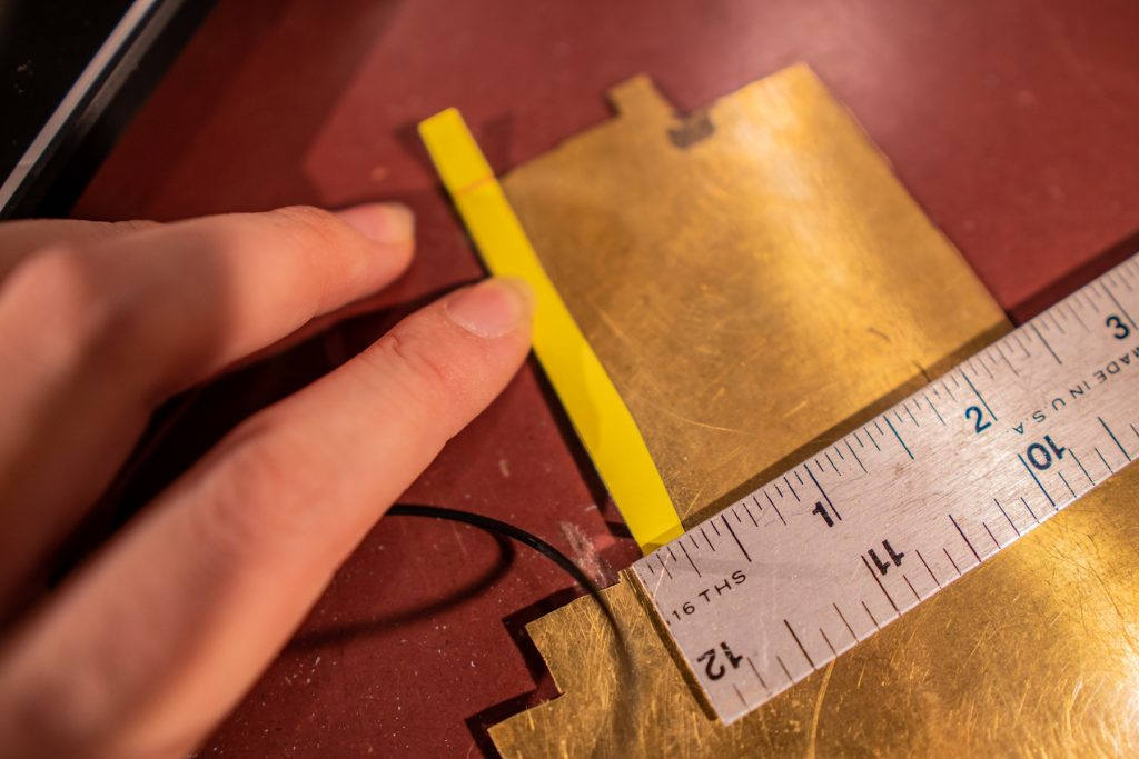 Cutting a sheet of brass into the preferred length and width.