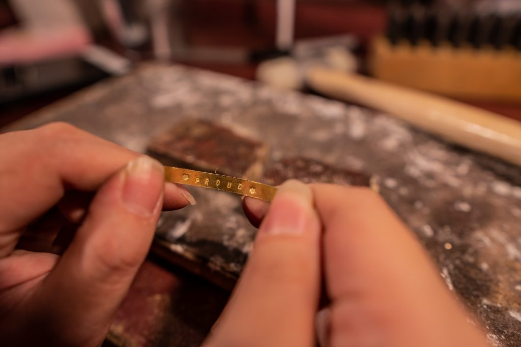 Stamping letters onto the inside of the ring.